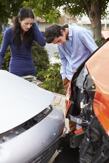 drivers examine car accident damage