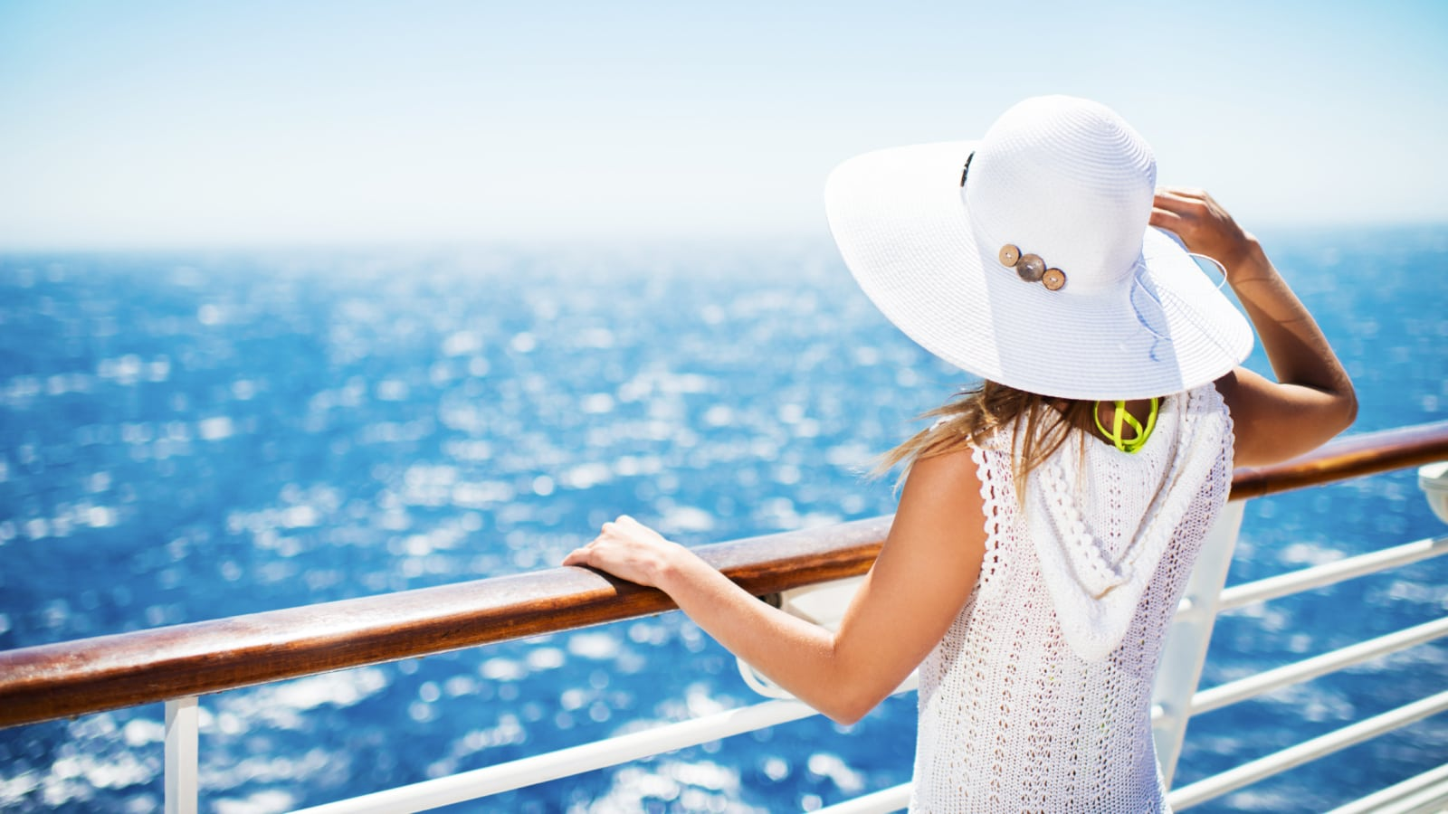Woman with hat on a cruise ship looking at the view.