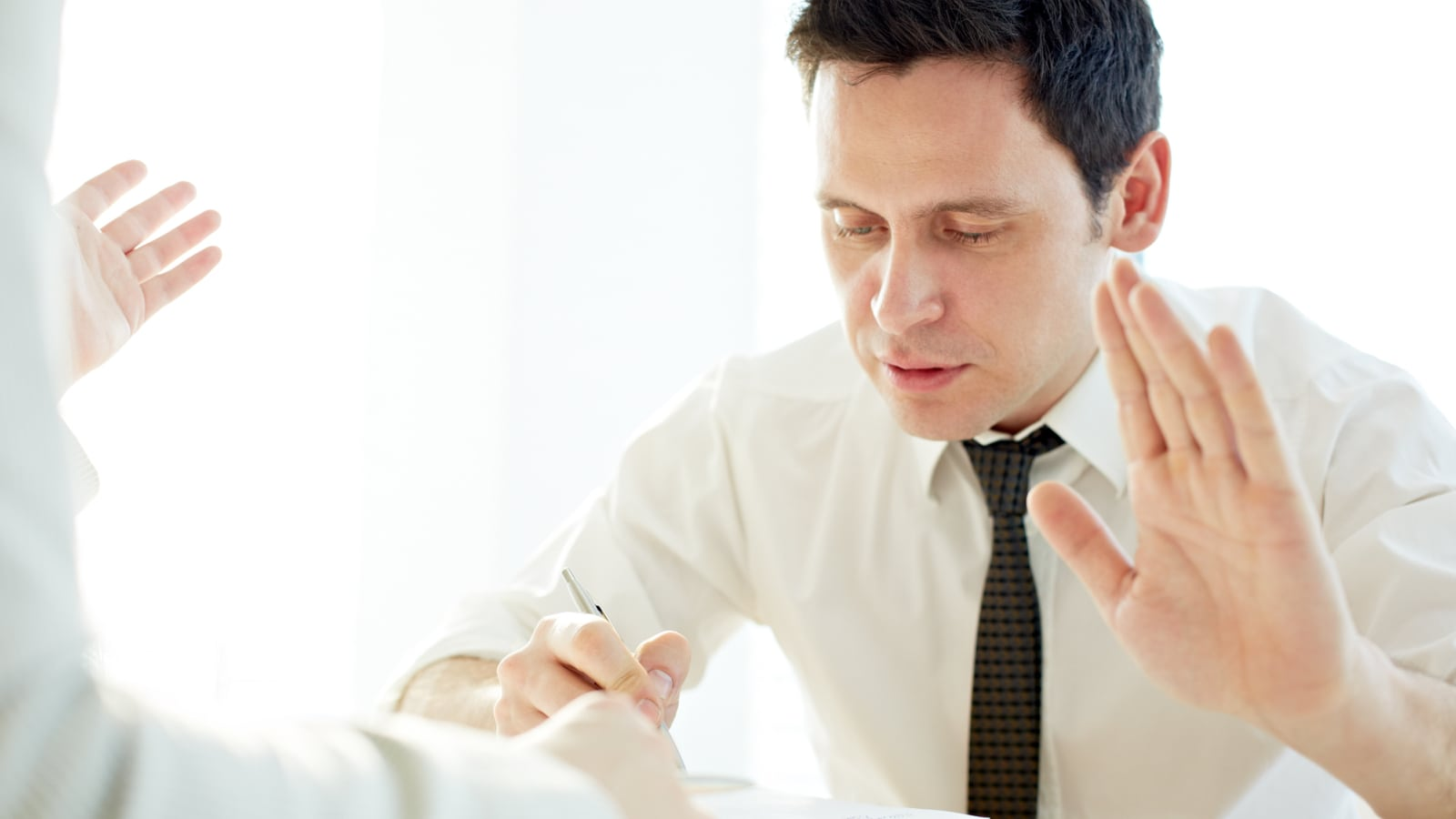 "Man showing ""stop"" while making notes at the table"