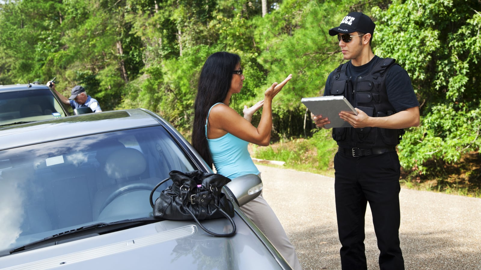 Policeman talks to woman driver after accident